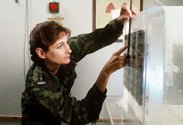Master Sgt. Jocelyn Nixon measures a radiation level at the Armstrong Laboratory Occupational and Health Directorate where she is the superintendent of the instrument calibration facility.  She is wearing a collar badge to gauge doses of radiation to the thyroid.  Nixon works primarily with the air Force Dosimetry Program which distributes, collects, and reads radiation badges worn by Air Force X-ray workers in the medical, dental, and industrial fields.  Published in Airman Magazine October 1996.